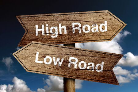 righteous: High Road And Low Road concept road sign with blue sky background.