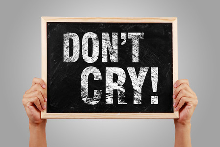 negatively: Do Not Cry blackboard is hold by hands with gray background. Stock Photo
