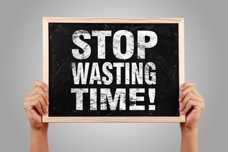 wasting: Stop Wasting Time blackboard is hold by hands with gray background. Stock Photo