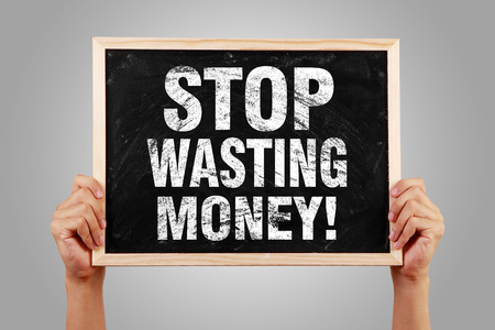 stop: Stop Wasting Money blackboard is hold by hands with gray background. Stock Photo