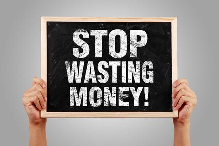 Verschwenden Sie Geld Tafel ist zu halten von Hand mit grauen Hintergrund. Standard-Bild - 37215107