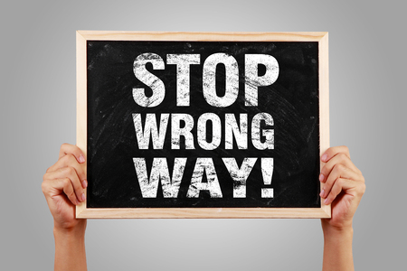 back problem: Stop Wrong Way blackboard is hold by hands with gray background.