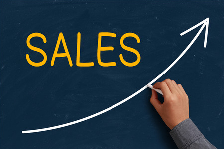 sales occupation: Sales Growth on blue chalkboard with the hand of businessman.  Stock Photo