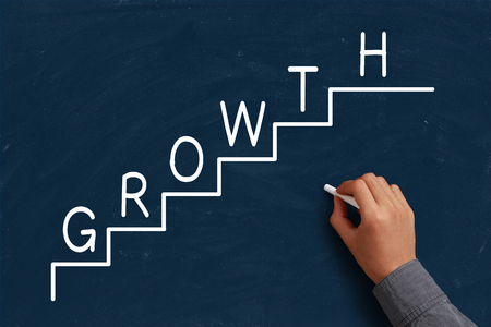 growth concept: Growth Concept on blue chalkboard with the hand of businessman. Stock Photo