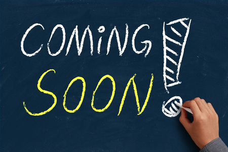 Coming soon on blue chalkboard with the hand of businessman. photo