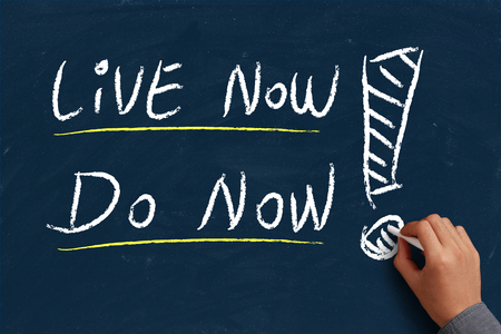 live work city: Live now do now on blue chalkboard with the hand of businessman.