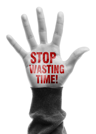 wasting: Hand with Stop Wasting Time text is isolated on white background. Stock Photo
