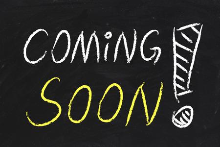 Coming Soon text is written by chalk on blackboard. photo