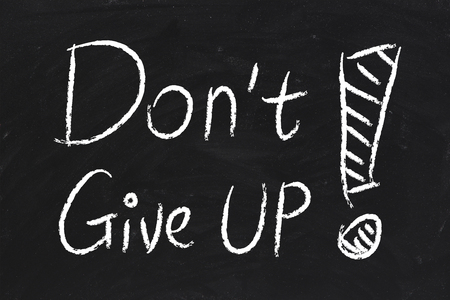 not give: Do Not Give Up text is written by chalk on blackboard.