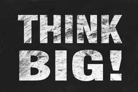 Think big text is written by white chalk on blackboard. photo