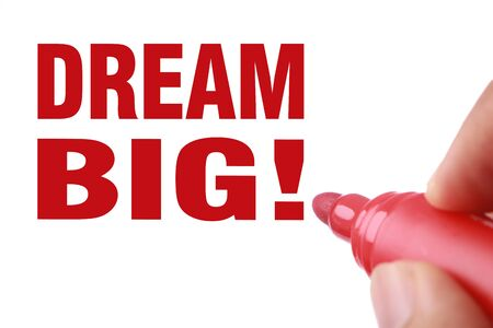 Dream big text is written by red marker on white paper. photo