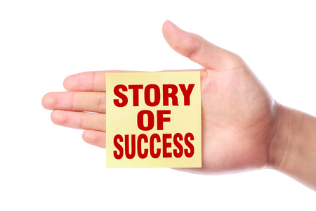 Hand with Story of success sticky note is isolated on white background. photo