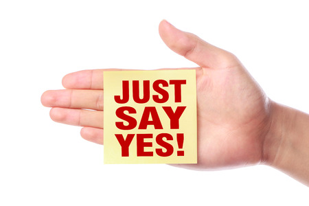 just ahead: Hand with Just say yes sticky note is isolated on white background.