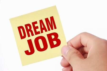 Hand with Dream job sticky note is isolated on white background. photo