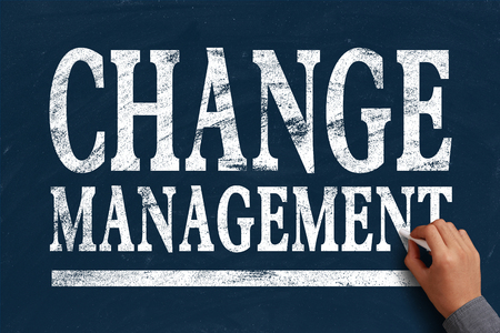 Businessman is writing Change management text on blue chalkboard. photo