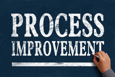 Businessman is writing Process improvement text on blue chalkboard. photo