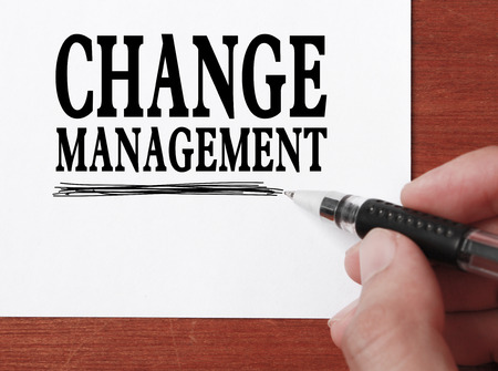 Businessman is writing Change management text on white paper. photo