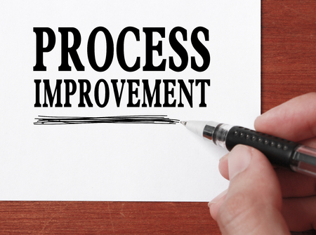 Businessman is writing Process improvement text on white paper. photo