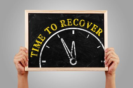 recover: Hands are holding the blackboard of time to recover concept against gray background.