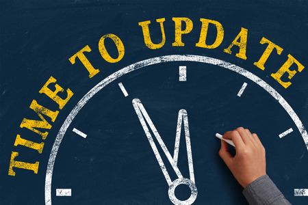 Businessman is drawing the concept of time to update on chalkboard. photo