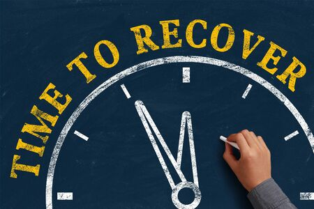 recover: Businessman is drawing the concept of time to recover on chalkboard.