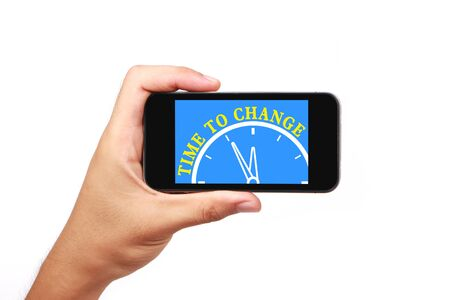 Hand is holding the smartphone of time to change concept isolated on white background. photo