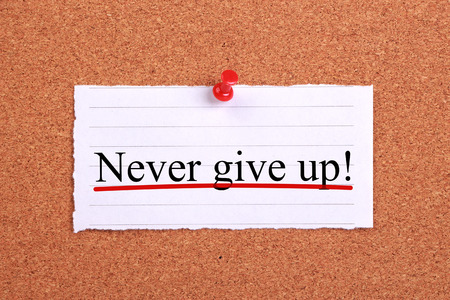 give up: Never give up text paper is pinned on cork.
