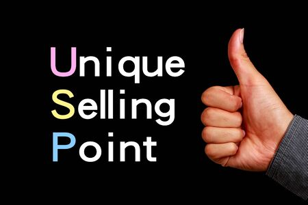 selling points: USP concept is on the blackboard with thumb up hand aside.