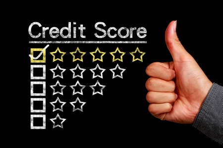 credit report: Credit score concept is on the blackboard with thumb up hand aside.