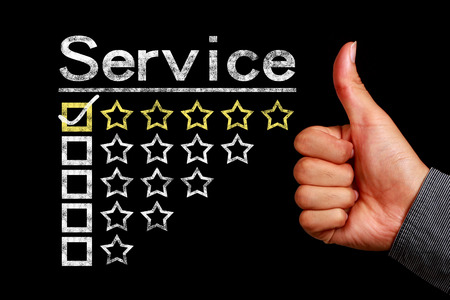 testimonial: Service concept is on the blackboard with thumb up hand aside.