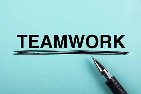 Teamwork text is on blue paper with black ball-point pen aside. Stock Photo