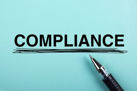 Compliance text is on blue paper with black ball-point pen aside. Stock Photo
