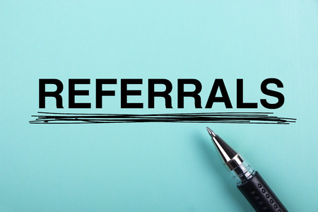 word of mouth: Referrals text is on blue paper with black ball-point pen aside.