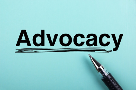 urging: Advocacy text is on blue paper with black ball-point pen aside. Stock Photo