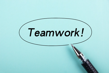 harmonize: Teamwork text is on blue paper with black ball-point pen aside. Stock Photo