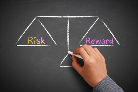investment risks: Hand with chalk is drawing Risk and reward balance scale on the chalkboard.