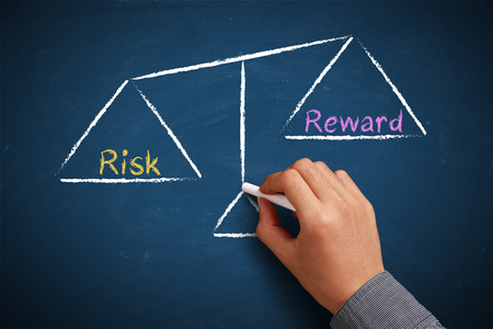 Hand with chalk is drawing Risk and reward balance scale on the chalkboard.