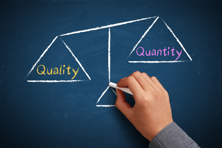 quantity: Hand with chalk is drawing Quality and quantity balance scale on the chalkboard.