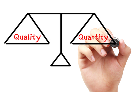 quantity: Hand with marker is drawing Quality and quantity balance scale on the transparent white board. Stock Photo