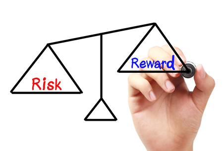 risky job: Hand with marker is drawing Risk and reward balance scale on the transparent white board.