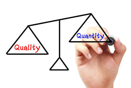 unequal: Hand with marker is drawing Quality and quantity balance scale on the transparent white board. Stock Photo