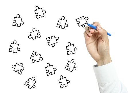 things that go together: Businessman is drawing puzzles with blue marker on transparent board isolated on white background. Stock Photo