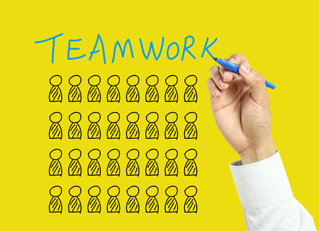 board marker: Businessman is drawing Teamwork concept with marker on transparent board with yellow background.