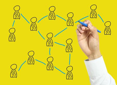 board marker: Businessman is drawing social network concept with marker on transparent board with yellow background.