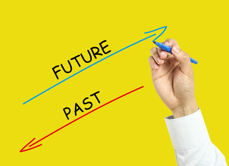 Businessman is drawing future and past concept with marker on transparent board with yellow background. photo