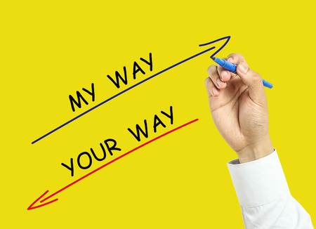 Businessman is drawing my way and your way concept with marker on transparent board with yellow background. photo