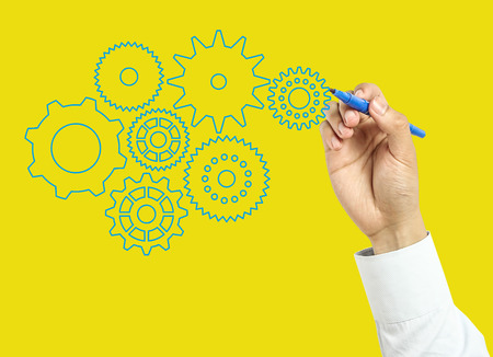 Businessman is drawing gears with marker on transparent board with yellow background. photo
