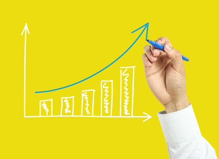 Businessman is drawing growth graph with marker on transparent board with yellow background. photo