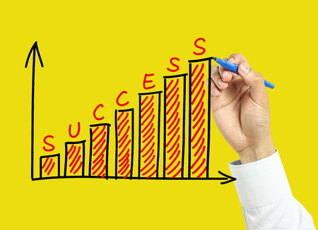Businessman is drawing success graph concept with marker on transparent board with yellow background. photo
