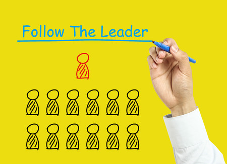 Businessman is drawing follow the leader concept with marker on transparent board with yellow background. photo